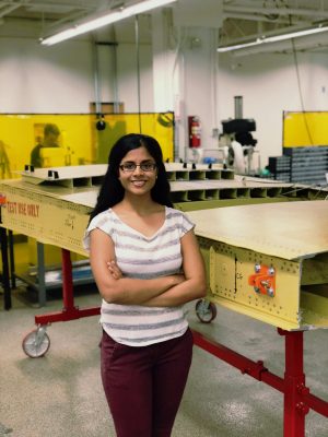 Krithika stands next to a model wing at the Boeing Advanced Research Center at UW.